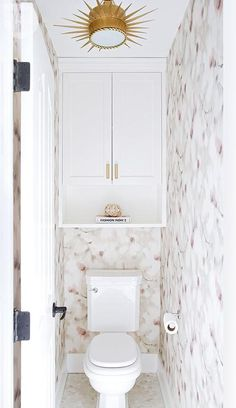 Corea Sotropa Interior Design - Chic water closet is clad in pink and gray floral wallpaper lined with a cabinet and shelf hovering over a toilet illuminated by a Soleil Small Pendant.