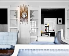 French doors + sun burst wall mirror + black and white wainscoting + couch on the left. #livingroom #interiordesign
