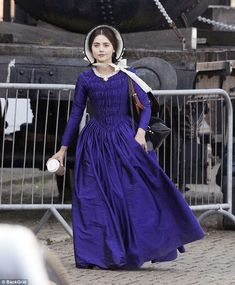 Modern queen:Jenna Coleman looked to be quite the time traveller as she was spotted in full regalia on Wednesday - while carrying a disposable coffee cup during her break