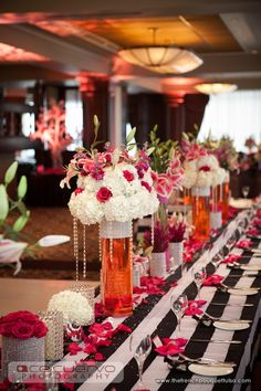 Pink and White Centerpieces with Pink Colored Water in Tall, Cylindrical, Glass Vases. HATE the rhinestone vases next to the bedazzled vases...