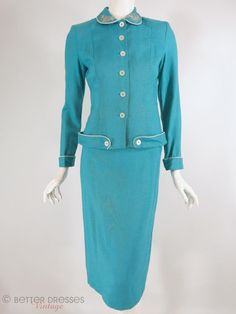 Beautifully tailored early 1950s skirt suit in teal blue linen-weave fabric, piped in white. Extensive seaming and darts for feminine shaping, with flattering hip accents. Rounded collar has hand-appl