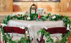 A sweetheart table is decorated with flowing greenery and flowers in front of an outdoor fireplace during a winter wedding near Austin, Texas.