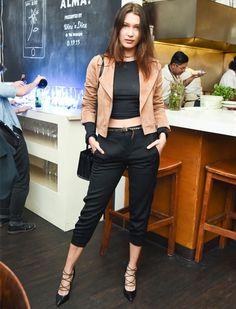 Look de Bella Hadid, com top cropped e calça pretos + jaqueta biker marrom.