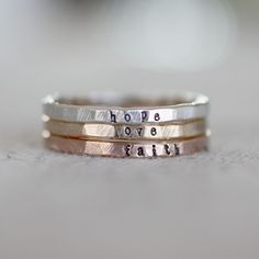 Teeny band rings I have one with all three of my children's names and I wear it with my wedding rings.