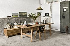 distressed concrete floors + wall siding / warm wood furniture / hanging brass light