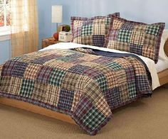 This richly patch-worked quilt, summons a subtle country Americana feel to your bedroom. Our Plaid Quilt couples a variety of plaids  in Deep Red, Hunter Green, Moss Green, Tan, Navy Blue, Cream and White. The reverse is Navy Blue. Will add such charm to your bedroom decor