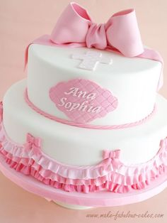 A sweet baptism cake decorated with pink ombre ruffles and cute fondant bows, perfect for a little girl christening.