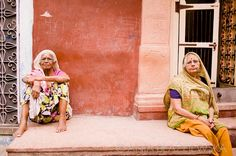 India, Jodhpur. Two Rajasthani women resting near their house in the old part of Jodhpur.