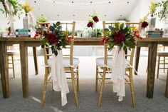 Fall wedding chair decor idea - romantic, red flowers with greenery and white fabric {Sarah Rizy ofLightly Photography
