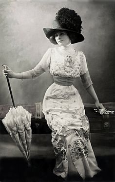 1900s daytime Dress: Edwardian day dress. Woman is wearing a Peg Top silhouette dress with hat and holding a parasol. Narrow skirt and empire waistline.
