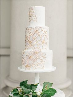 This white and gold wedding cake is absolutely stunning. Love the delicate detailing!