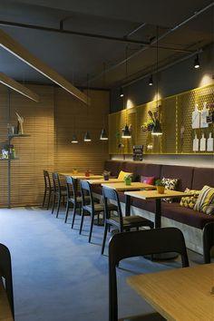 Galeria da Arquitetura | Boulangerie - O balcão de atendimento tem acabamento simples e cru, em madeira pinus, enquanto as mesas são funcionais e de variados tamanhos para fugir do estilo 'refeitório, usual em mostras de decoração