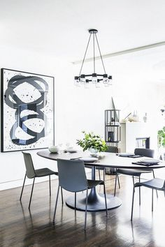 Dining space with dark wood floors, a pendant chandelier and large artwork
