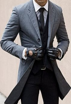 Go for a classic style in a grey overcoat and black striped dress pants. Shop this look for $264: http://lookastic.com/men/looks/dress-shirt-tie-dress-pants-belt-gloves-waistcoat-overcoat/5338 — White Dress Shirt — Black Tie — Black Vertical Striped Dress Pants — Dark Brown Leather Belt — Dark Brown Leather Gloves — Black Vertical Striped Waistcoat — Grey Overcoat