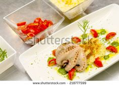 octopus with mashed potato in a delicious composition plate with cherry tomato and pesto sauce - stock photo