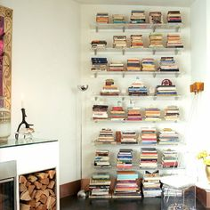 """Displaying Books: Perspex Shelves: Colourful Spines""""A pleasing way to arrange books of different sizes is to stack them horizontally in tapered stacks. Pile the largest books on the bottom shelves to ensure the effect doesn't become top-heavy. Place small ornaments on top of some stacks to complete the pyramid effect."""