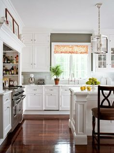 white cabinets, marble counters, wood floors, graphic roman shade