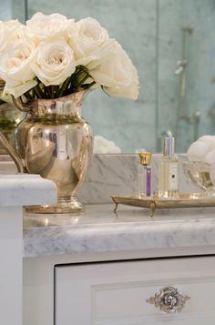 flowers in a silver milk pourer. classic bathroom decorum