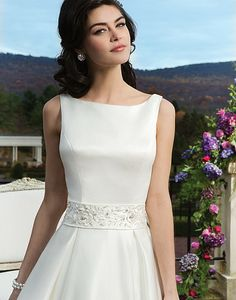 Sincerity wedding dress style 3810 is a matte satin ball gown featuring box pleats, a bateau neckline and an embroidered and beaded detachable matte satin belt.