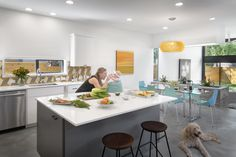 In the airy kitchen, meals are prepared on a Silestone White Storm countertop. The backsplash's tiles match those on the staircase's risers. In the adjoining dining area, a Caboche suspension light by Foscarini hangs over a CB2 dining table and Real Good Chairs by Blu Dot.