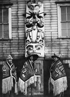 Tlingit men in regalia, including a spruce-root crest hat with potlatch rings (center), Killer Whale crest hat (right) and Chilkat robes. Each man holds a Raven rattle.    Courtesy of the Alaska State Library, Elbridge W. Merrill Photograph Collection, P57-022.