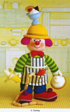 "From 'Knitted Clowns', Pt.1 of Jean Greenhowe's 'Red Nose Gang' collection meet the scrumptious O. Yummy. He is knitted with DK wool and stands 30cm/12"" tall (excl. hat decor). He has all he needs to put on a lovely spread. Designed and published by Jean Greenhowe Designs in 1992."
