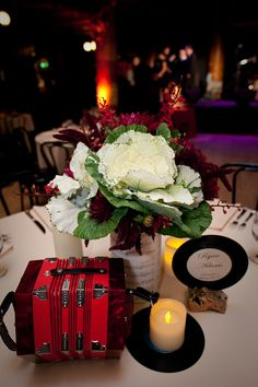 """Vintage insturments, vases wrapped in vintage sheet music, table """"numbers"""" are old 45's for a music themed wedding at the American Music Hall"""