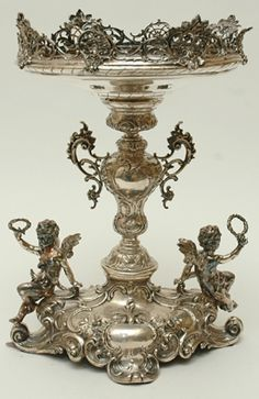 Continental Silver Centrepiece The chased and embossed central standard flanked by pierced and foliate moulded handles, rising to a shallow circular bowl with a pierced rim, raised on a lobed serpentine base with applied putti, hallmarked.
