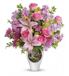 Fill their day with love and light! Hand-delivered in our graceful vase adorned with Thomas Kinkade 's Garden of Grace painting, this lush bouquet of roses and lilies delights the senses with its beauty and fragrance. It 's a gift that will live on in their heart for years to come.Pink roses, pink asiatic lilies, lavender alstroemeria, lavender stock and lavender cushion spray chrysanthemums are arranged with bupleurum, huckleberry and lemon leaf.