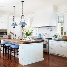 White cabinets w/crown moulding, range hood, pot filler, Delft tile backsplash, butcher block on island, roman shades, pendants