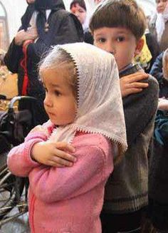 sweet little girl with arms crossed leading to communion (Orthodox church, I'm guessing)