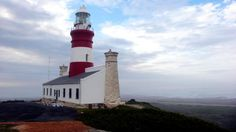 Cape Agulhas Lighthouse, South Africa. 27 metre white round tower painted with red bands. Date Installed: 1 March 1849. It is situated at the southern most tip of Africa. It was modelled on one of the seven wonders of the ancient world, the Pharos of Alexander.
