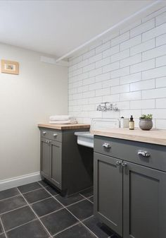 Gray laundry room features an accent wall clad in white brick tiles accented with gray grout lined with charcoal gray shaker cabinets adorned with polished nickel cup pulls topped with light wood countertops flanking a wall mount vintage sink alongside a charcoal gray tiled floor laid out in grid formation.