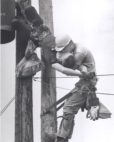 """Rocco Morabito won the 1968 Pulitzer Prize for Spot Photography for this photograph – """"The Kiss of Life.""""    Apprentice lineman J.D. Thompson is breathing life into the mouth of another apprentice lineman, Randall G. Champion, who hangs unconscious after receiving a jolt of high voltage.     Morabito was driving on West 26th Street in July 1967 on another assignment when he saw Champion dangling from the pole.  He called an ambulance and grabbed his camera. Champion recovered."""