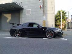 Black Nissan Skyline GT-R 34 next to Building Godzilla, Nissan Gtr R34, Gtr R35, Tuner Cars, Jdm Cars, Street Racing Cars, Auto Racing, Drag Racing, Nissan Infiniti