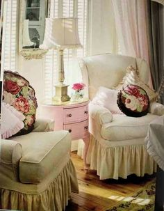 Cozy cottage seating area with needlepoint cushions, pink table and multi-hued drapes.