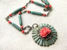 Found object pendant made from light fixture trim piece, filigree and a coral pink resin rose.