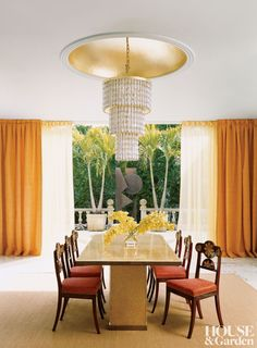 In the dining room of a Palm Beach, Florida, home, a cast-glass table by interior designer Ernest de la Torre with reverse gold leaf sits beneath a chandelier from the Waldorf-Astoria hotel. Russian neoclassical chairs and the curtains feature hints of red, orange, and gold.  DESIGNER: De la Torre Design Studio PHOTOGRAPHER: Jason Schmidt