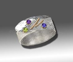 Sterling Silver / Gold Ring Hand polished, hammered sterling silver ring with 14K gold bezels and bars. Wide band appx. 12mm. Peridot, Amethyst and Sapphire Stones