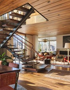 """Airy Stair. Smack in the middle of this apartment's living and dining spaces sits the stairway (pictured above), an element that could easily have blocked the view to the expansive terrace. The material of choice: slices of old-growth black walnut from Oregon, their organic live edges intact to distract from the room's rigid geometry. The answer to making the steps """"a feature but not an obstacle,"""" & risers between the heavy treads and using 1/8-inch bronze cable instead of traditional…"""
