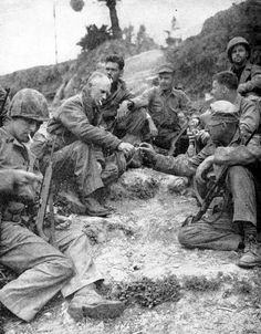 Ernie Pyle shares a cigarette with Marines on Okinawa 1945.  Pyle, a correspondent, was later killed by a Japanese bullet.