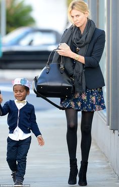 Chic crowd: The two-year-old was elegantly dressed in a  white shirt, black cardigan and black trousers while his 39-year-old actress opted for a floral mini-dress that showed off her long, slender legs