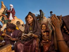 Their hands stained by the indigo dye in their new clothes, Tuareg women celebrate a birth. Tuareg females rarely cover their faces, while men traditionally wear turbans that conceal all but their eyes.