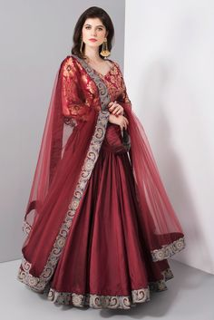 Bordeaux and gold brocade printed blouse with elbow length sleeves. Bordeaux poly dupioni silk lehenga with floral embroidered border. Matching net dupatta. Padded Blouse.