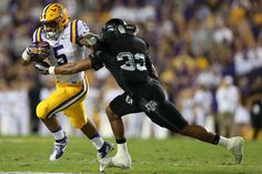 Shaan Washington Photos Photos - Derrius Guice #5 of the LSU Tigers is tackled by Shaan Washington #33 of the Texas A&M Aggies at Tiger Stadium on November 28, 2015 in Baton Rouge, Louisiana. - Texas A&M v LSU