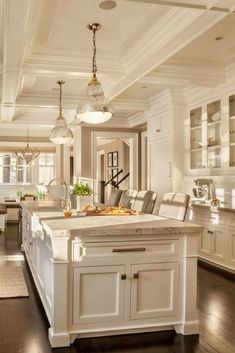 Gorgeous kitchen design. Look at the details in the ceiling and custom island. White with dark wood flooring - classic look.