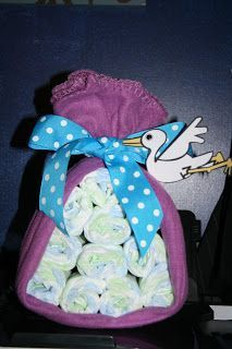 Wal-Mart receiving blanket wrapped around rolled up diapers. Add a ribbon bow and a stork. Easy cute gift!