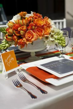 Orange rose and tulip floral centerpiece and orange and ivory wedding reception place setting for a fall wedding