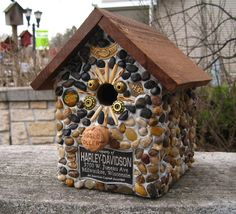 """Harley Davidson Motorcycle motif birdhouse. Cedar birdhouse with stones and river rock collected from the shores of Lake Michigan, local rivers and from creek beds.  Recycled embellishments of Harley Davidson rocker, pins, HD plaque and beads enhance the theme. The perch is a champagne cork. Suitable for outdoor or indoor décor. 7 3/4 """" wide X 9"""" high X 9"""" deep   ( 1 1/8"""" opening)   http://www.stonedbirdhouse.com/"""