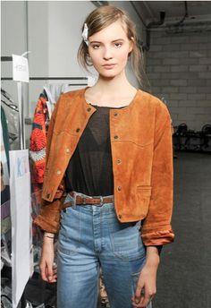 Kort suéde jackje gecombineerd met een high waist jeans en doorschijnende top.